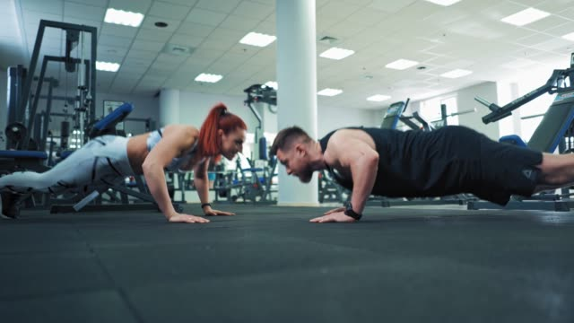 Bидео Muscular athletic man and beautiful fitness woman doing push ups exercise indoors.