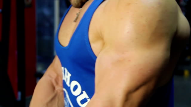 Muscular biceps of strong professional bodybuilder doing barbell curls at gym