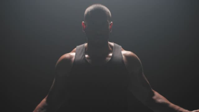 muscular black man jumping rope on a dark background, in slow motion - irriducibilità video stock e b–roll