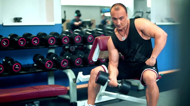 Muscular bodybuilder guy doing exercises with dumbbells in the gym. video
