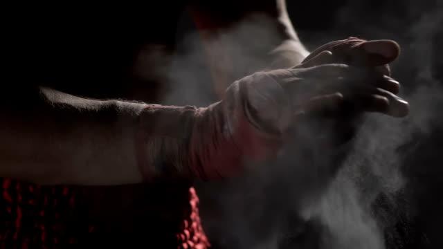 vídeos de stock e filmes b-roll de muscular boxer clapping together hands with talcum powder, boxing workout - boxe tailandês
