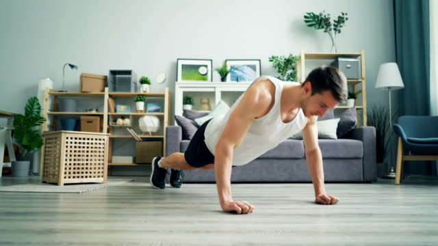 Muscular dark-haired guy doing pushup working out at home in comfortable clothes Muscular dark-haired guy is doing pushups working out at home wearing comfortable sports clothes and sneakers. Beautiful light apartment is visible in background. push ups stock videos & royalty-free footage