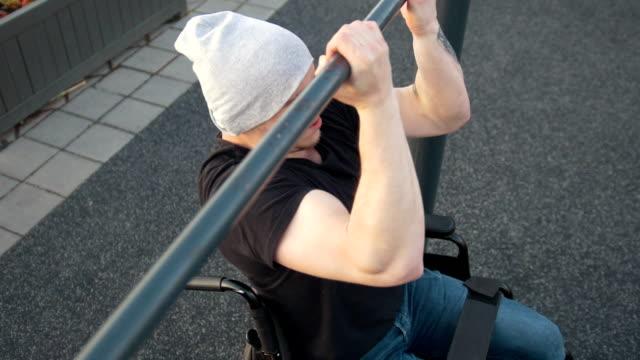 vídeos y material grabado en eventos de stock de hombre con discapacidad en silla de ruedas tira de la barra al aire libre - deportes en silla de ruedas