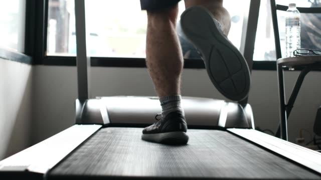 vídeos de stock e filmes b-roll de muscular feet in sneaker running on treadmill in gym - aparelho de musculação