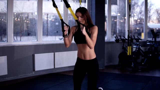 Muscular, fitness girl in black sportswear doing legs exercises while holding weight straps. Squatting, bonding legs, lift high the knees. Grey coloured, modern gym. Slow motion video