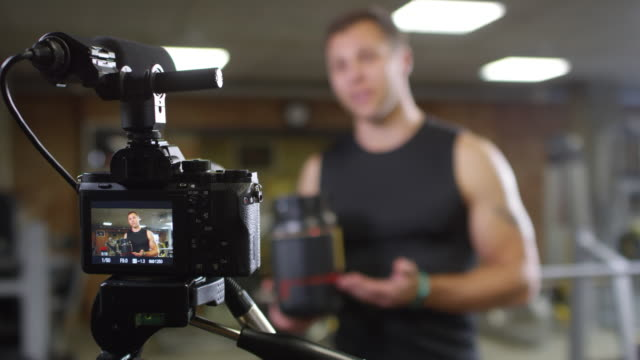 muscular fitness trainer telling about dietary supplements on camera - integratore vitaminico video stock e b–roll