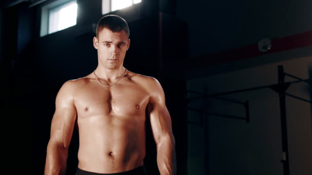 Muscular handsome man standing in large gym video