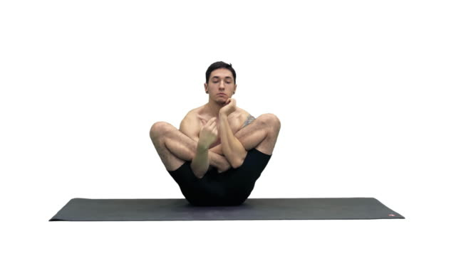 Muscular handsome young man working out, yoga, lotus, hands on the face on white background