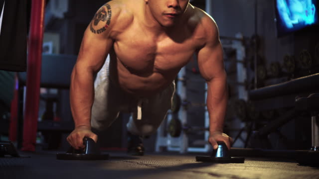 Muscular man doing push-ups on dumbbells in gym video