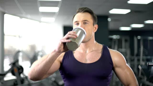 vídeos de stock, filmes e b-roll de homem musculoso bebendo batido de proteínas após o treino, dieta saudável, musculação - medicina esportiva