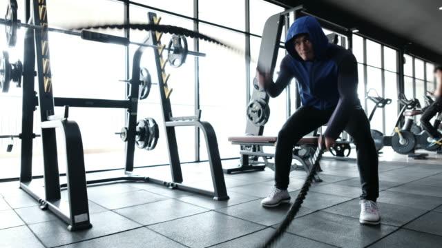 vídeos y material grabado en eventos de stock de hombre musculoso haciendo ejercicio con cuerdas - entrenamiento con pesas