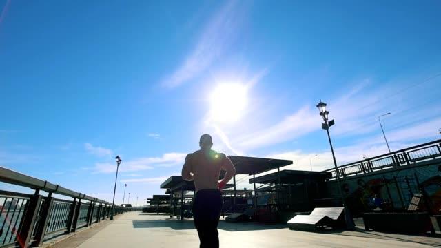 muskulös man jogging på strandpromenaden i soliga dag, slow motion - tävlingsdistans bildbanksvideor och videomaterial från bakom kulisserna