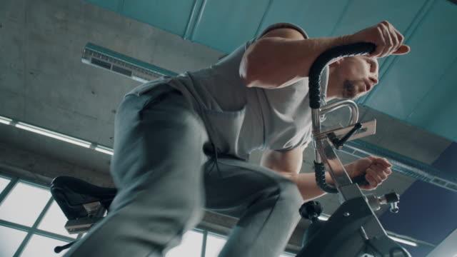 vídeos de stock e filmes b-roll de muscular man on exercise bike - aparelho de musculação