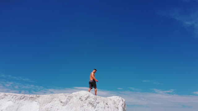 Muscular man on white hill