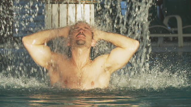 HD SLOW MOTION: Muscular Man Relaxing Under Spa Waterfall video
