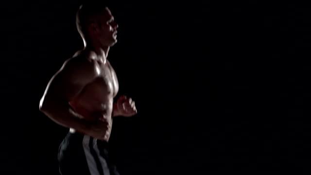 Muscular man running in profile, medium shot left video
