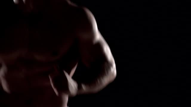 Muscular man running towards camera, torso shot close left video