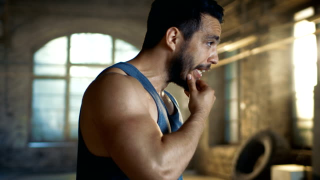 Muscular Man Wipers Sweat of His Forehead after Intensive Cross Fitness Bodybuilding Training. He Wears Sleeveless Shirt and Works out in a Gym. video