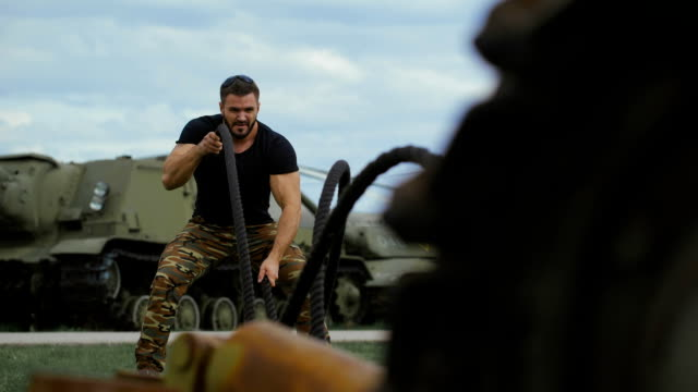 Muscular military man made a gym training at a military base video