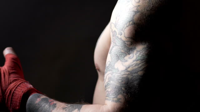 Muscular Muay Thai boxer with tattoos pulling bandage on his hand, slowmotion video