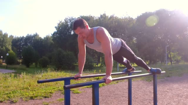 muscular sportsman bodybuilder gymnast is making push ups on bars in city park. - man city exercise abs video stock e b–roll