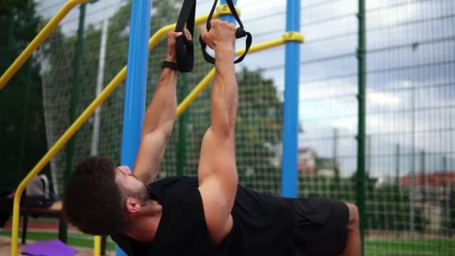 muskularny sportowiec robi wiszące pull ups ćwiczenia za pomocą paska do siły strenth treningu na zewnątrz - trening siłowy filmów i materiałów b-roll