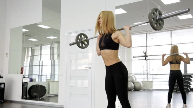 A muscular woman athlete using the barbell with weights, trains on the squats. buttocks, ass in the gym video