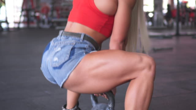 muscular woman doing squat exercise with kettlebell - pantaloncini video stock e b–roll