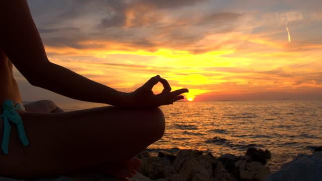 närbild: muskulös kvinna på steniga ocean beach i lotusställning yoga i solnedgången - korslagda ben bildbanksvideor och videomaterial från bakom kulisserna