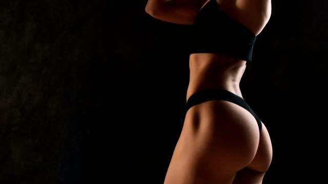 暗い背景のスタジオで筋肉の若い女性は、さまざまな動きと完璧な体の部分を示しています。腹筋とお尻のクローズ アップ - 筋肉質点の映像素材/bロール