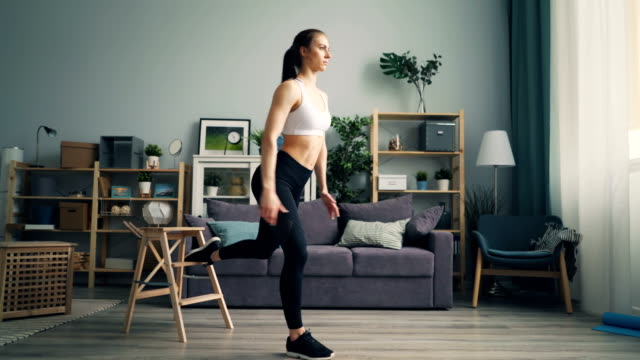 vídeos de stock e filmes b-roll de muscular young woman is doing squats indoors concentrated on physical exercise - treino em casa