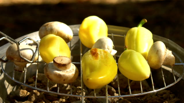 Mushroom, pepper grilling on a barbecue, turn using barbeque tongs