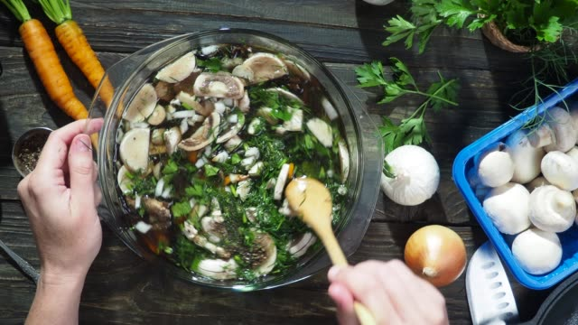 Mushroom soup cooking Cooking mushroom soup with fresh champignons and vegetables. Stirring the soup in the pan. Overhead view ingredient stock videos & royalty-free footage