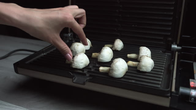 mushrooms on bbq. mushrooms are cooking over electric hot bbq grill. female hands with a beautiful manicure puts mushrooms champignons - articoli casalinghi video stock e b–roll