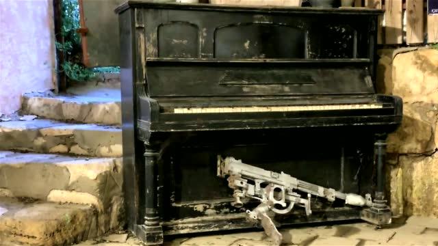 vidéos et rushes de musique et guerre. piano antique et mitrailleuse blindée sur le plancher de pierre hd - mitrailleuse