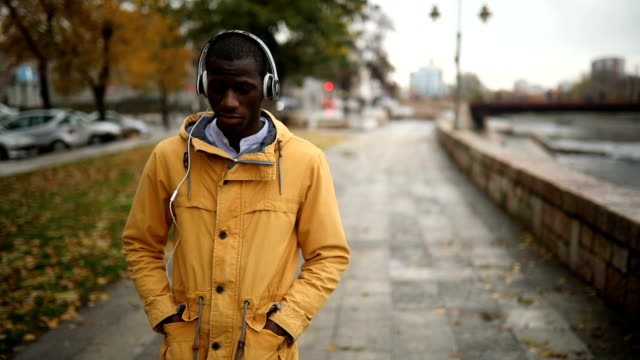 Music anywhere Young African man relaxing and enjoying autumn in the public park, using phone headphones stock videos & royalty-free footage