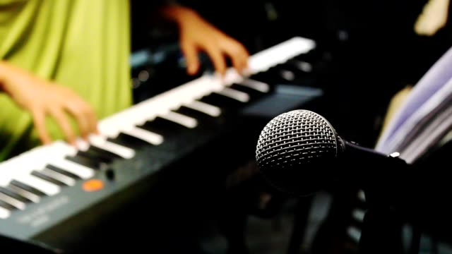 Music band concept background.Selective focus microphone and blurred man playing electric piano.Mix variety object on the modern home recording.An idea musician play the instruments at the studio. video