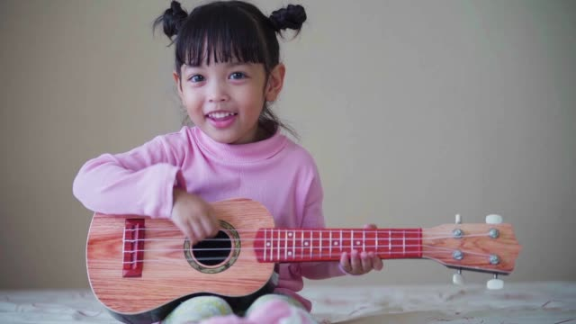 music concept. happy kid playing guitar with happiness at home. (slow motion) - etnia malese video stock e b–roll