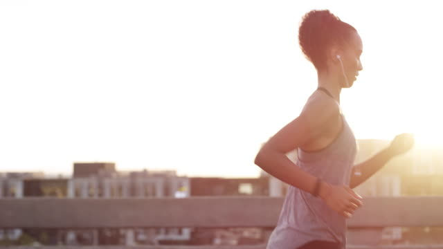 vídeos de stock e filmes b-roll de music gets the heart pumping - young woman running city