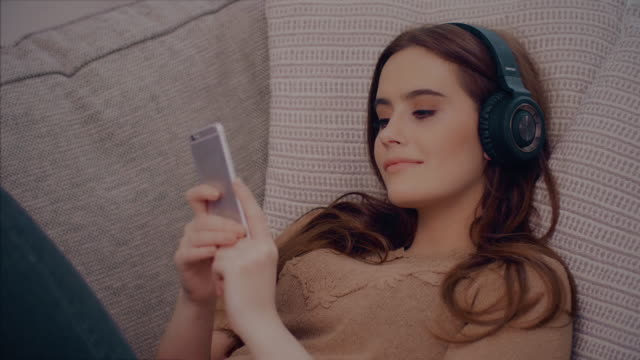 Music headphones, relaxing on sofa. Beautiful young woman.