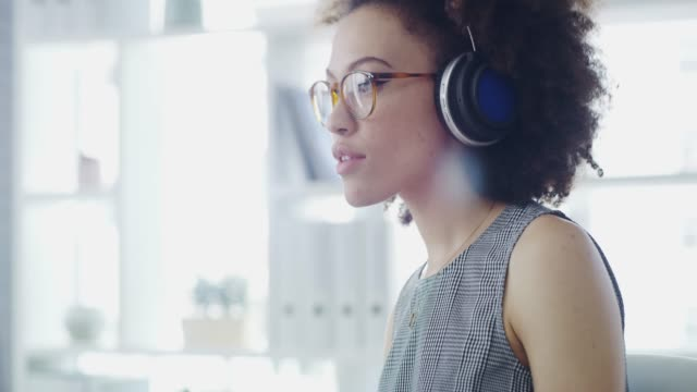 Music inspires positivity, positivity inspires productivity 4k video footage of a young businesswoman listening to music in a modern office headphones stock videos & royalty-free footage