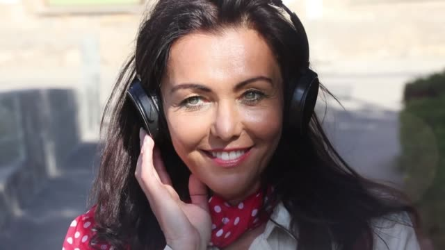 Music is the best therapy Video footage of a mature woman listening to music and flirting in rhythm. donna stock videos & royalty-free footage