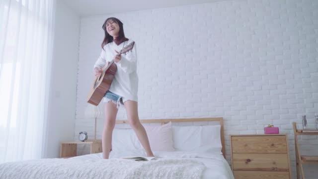 vídeos de stock, filmes e b-roll de conceito do amante da música. mulher bonita asiática que joga a guitarra e a dança em sua cama com divertimento. - música acústica