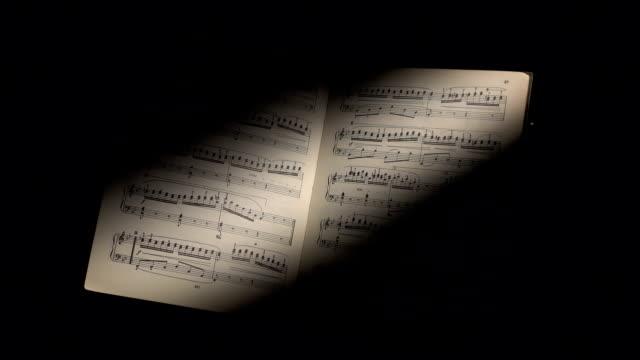 vídeos de stock e filmes b-roll de notas de música com raio de luz sobre preto - compositor