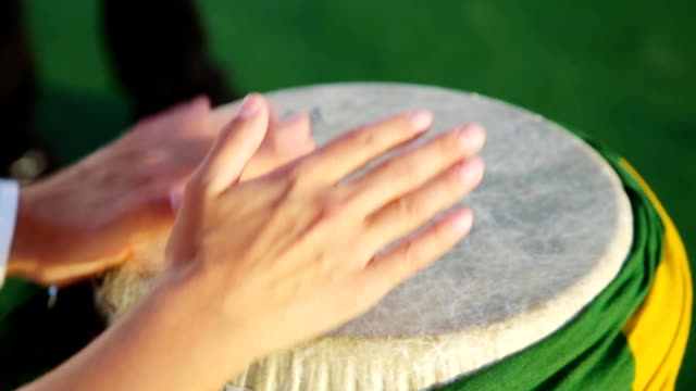 music played on drum wrapped with brazil flag. Hands only video