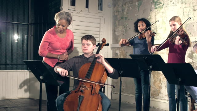 Music teacher, teenage students with string instruments