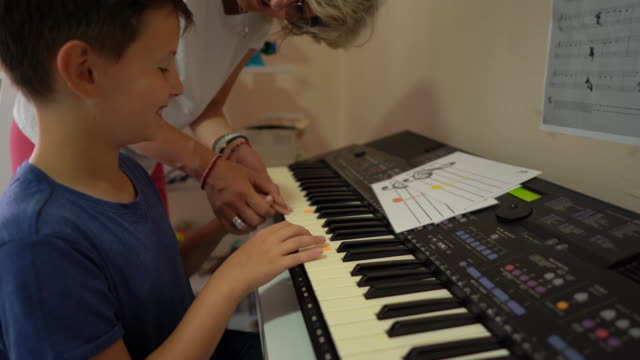Music therapist and boy playing synthesizer at rehabilitation center