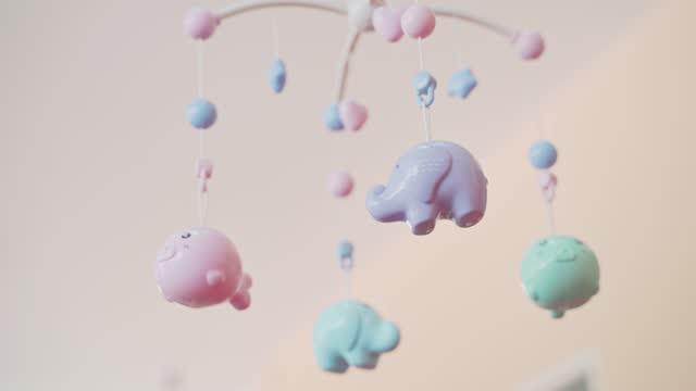 vídeos de stock, filmes e b-roll de celular bebê musical com brinquedos animais giram acima do berço bebê, vista para baixo. desenvolvimento de habilidades de bebê. - mobile