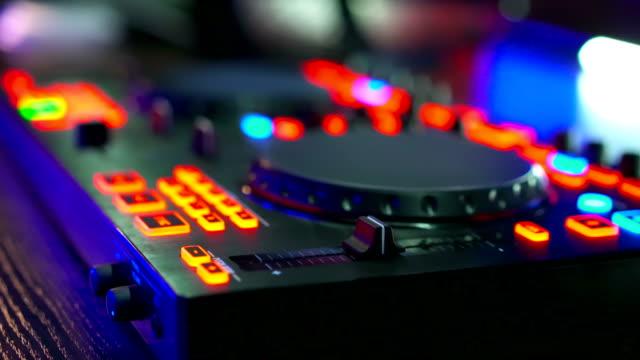 Musical equipment, DJ mixer on table at night club - vídeo