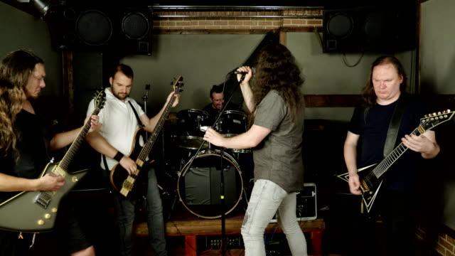 vídeos de stock e filmes b-roll de musical metal band. punk, heavy metal or rock group. musicians playing music on stage. 4k - bateria instrumento de percussão